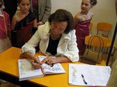 Paní Livia podepisuje školní kroniku ataké památníčky dětem.